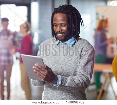 Smiling man using digital tablet in creative office