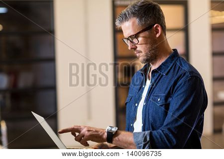 Concentrated man using laptop in creative office