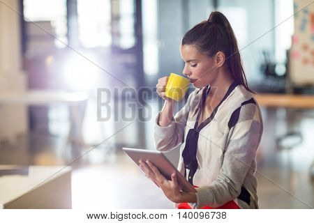 Young woman drinking coffee while holding digital tablet in office