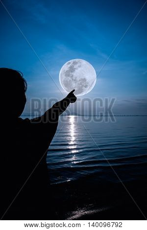 Silhouette Back View Of Woman Relax At Seaside And Pointing To The Full Moon. Outdoor.