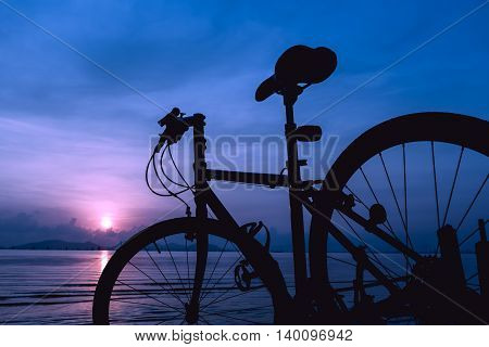 Silhouette Of Bicycle On The Beach Against Colorful Sunset In The Sea. Outdoors. Vintage