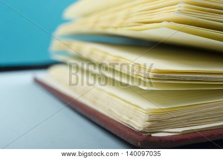 Macro view of book pages on colorful paper background. Copy space for text