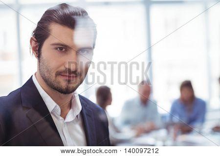 Portrait of confident businessman at office seen through glass