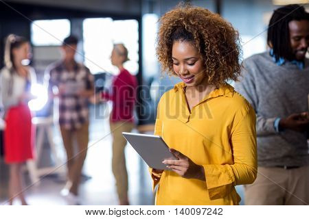 Young woman using digital tablet in creative office