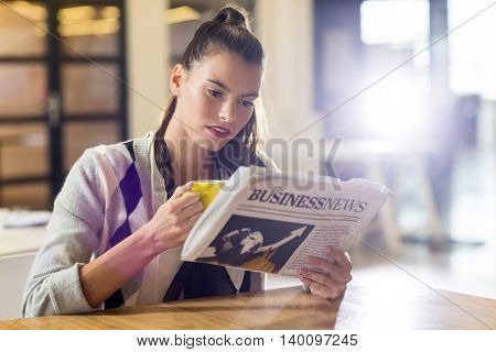 Young concentrated woman reading newspaper in office