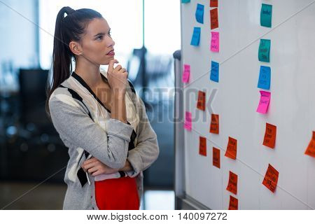 Young woman looking at adhesive notes in creative office