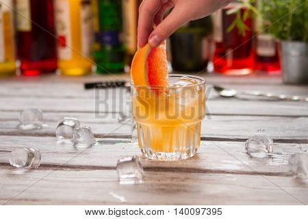 Orange drink in glass. Hand holds slice of grapefruit. Key ingredient for Cobas cocktail. Sweet and sour fruit.