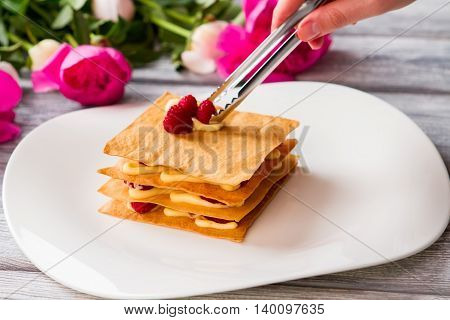 Shortcake with berries. Hand holding tongs. Chef prepares raspberry millefeuille. Layered dessert with sweet filling.