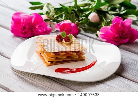 White powder falls on shortcake. Smear of red sauce. Fresh millefeuille with sugar. French pastry at local cafe.