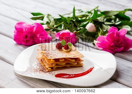 Dessert on a plate. Pink flowers on wooden surface. Millefeuille with chocolate crumbs. Baked food in french cafe.