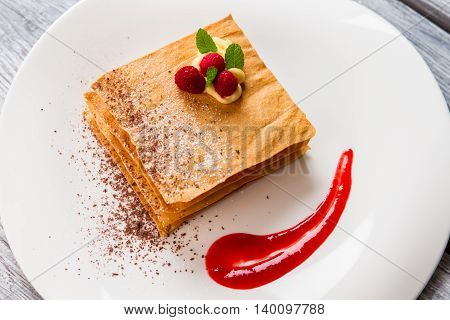 Pastry with yellow custard. Smear of sauce on plate. Millefeuille with raspberries and mint. Fine work by french chef.