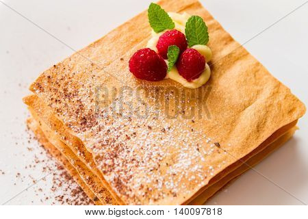 Pastry with mint and berries. Custard and chocolate crumbs. Expensive french dessert. Relax and enjoy your dessert.