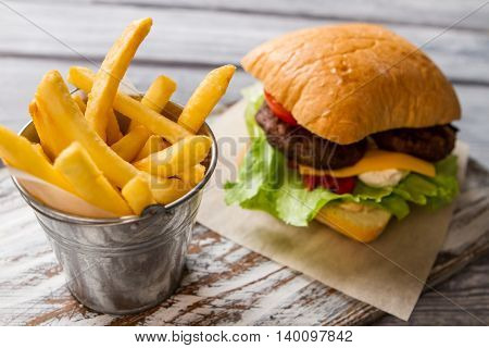 Burger and bucket with fries. Fresh lettuce and bun. Typical fast food snack. Beefburger with cream cheese.