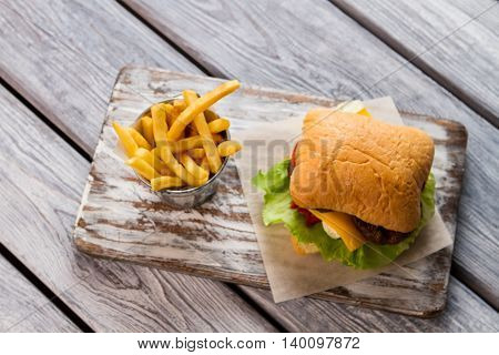 Bucket with fries on board. Top view of burger. Cheeseburger served at cafe. Snack that boosts energy.