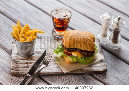 Burger with fries and cola. Cutlery on gray wooden board. Meal very high in calories. Hamburger with cream cheese.