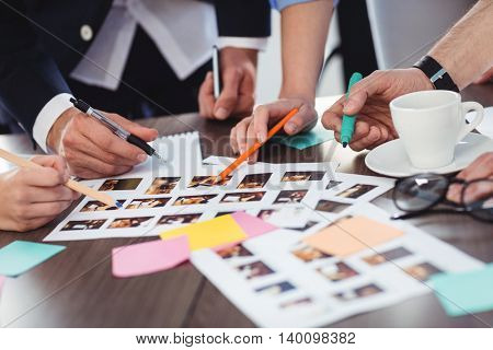 Cropped image of photo editors discussing about documents on table in meeting room at creative office