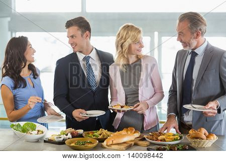 Business colleagues interacting while serving themselves at buffet lunch in a restaurant