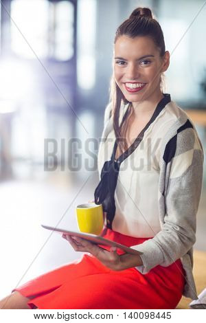 Portrait of smiling young woman holding digital tablet in creative office