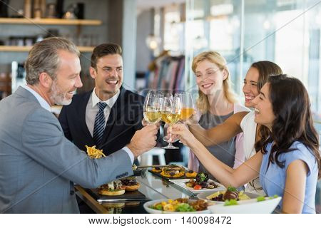 Happy business colleagues toasting beer glasses while having lunch in a restaurant
