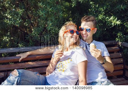 Young couple eating ice cream while sitting on the bench summer time