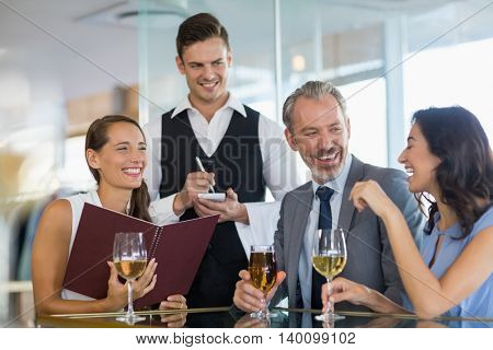 Waiter taking the order from a businessman and his colleagues in restaurant