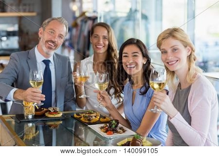Portrait of happy business colleagues holding beer glasses while having lunch in a restaurant