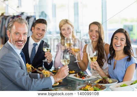 Portrait of happy business colleagues toasting beer glasses while having lunch in a restaurant