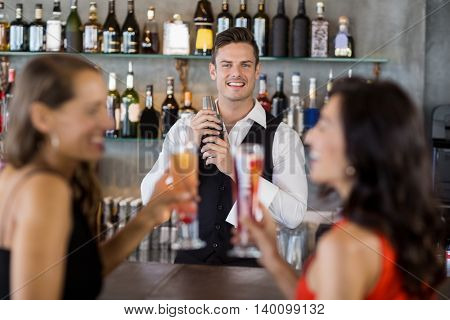Two women having cocktail while a waiter preparing cocktail with cocktail shaker in restaurant