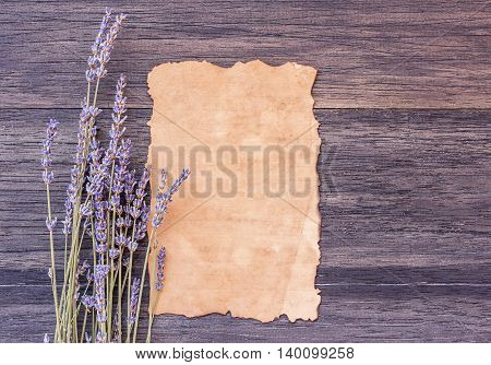 Old paper and lavender flower on dark wooden table background. top view with copy space