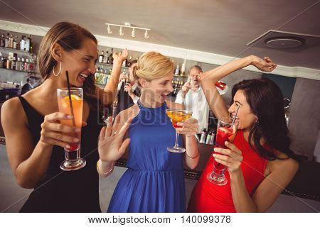 Female friends holding glass of cocktail while dancing in restaurant