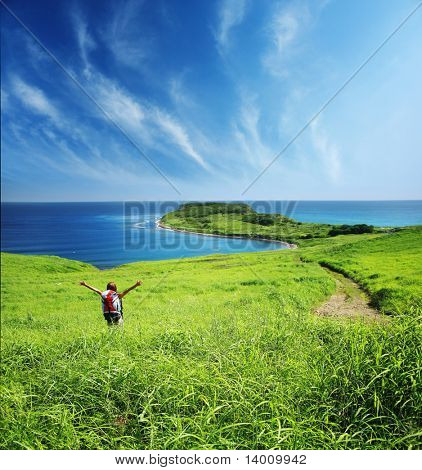 Men with rucksack in deep green grass near sea