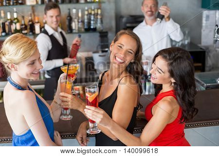 Happy female friends holding glass of cocktail at bar counter in restaurant