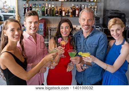 Group of friends toasting glass of cocktail in restaurant