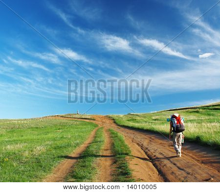 Women with backpack walking to top of hill