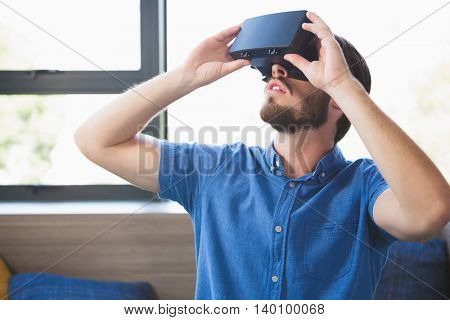 Close-up of man using virtual reality glasses at home