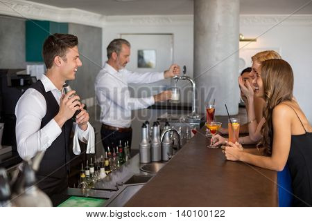 Beautiful women having cocktail while waiter preparing cocktail with cocktail shaker in restaurant