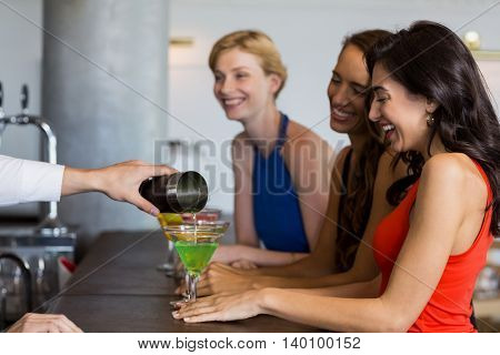 Waiter pouring cocktail into cocktail glass at bar counter in restaurant