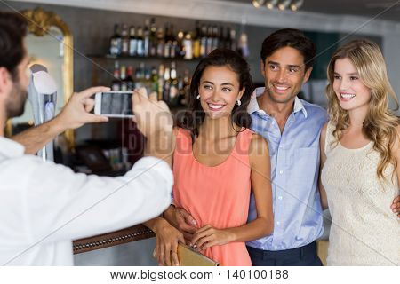 Man taking photo of his friends in restaurant