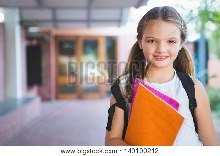 Portrait of happy schoolkid standing in corridor at school