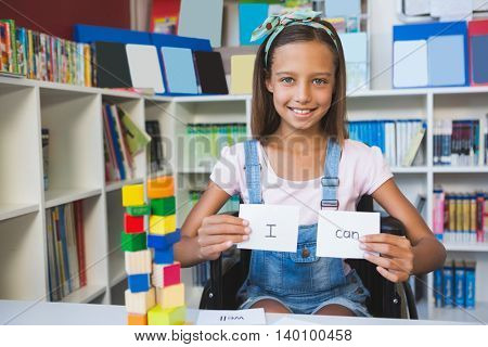 Disabled girl showing placard that reads I Can in library at school