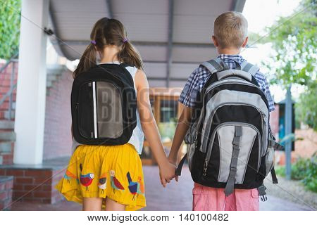 Rear view of schoolkids holding hands standing in corridor