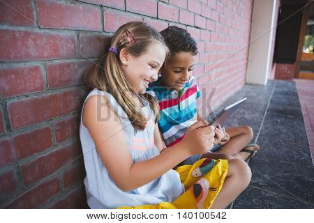Schoolkids sitting in corridor and using digital tablets at school