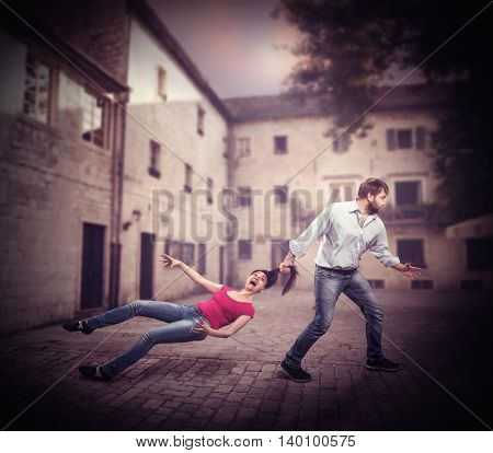 Angry man pulling woman by the hair on the road