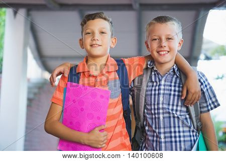 Portrait of smiling schoolkids standing with arm around in corridor at school