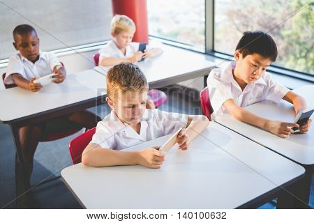 Schoolkids using mobile phone in classroom at school