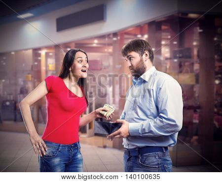 Woman taking money from husband's purse in the shopping mall
