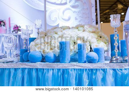 Wedding decorated hall with bouquet and blue candles