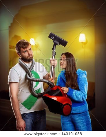 Wife asking her husband to clean the room with vacuum cleaner