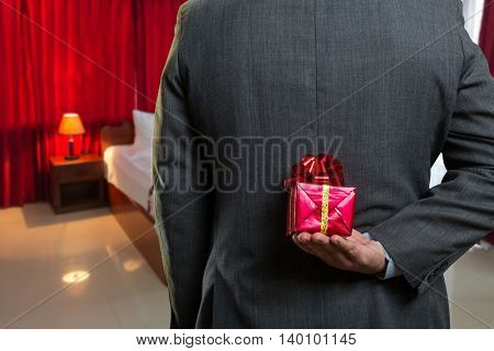 Businessman hiding a gift behind his back closeup
