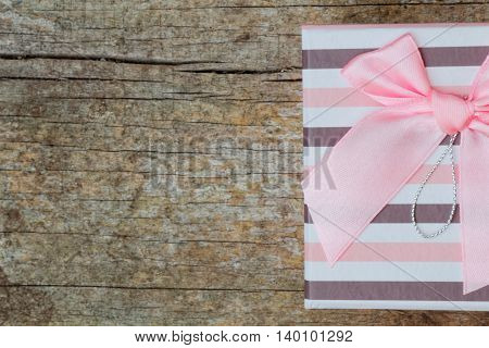 A striped present with pink bow half shown in the image with space for text on its right side